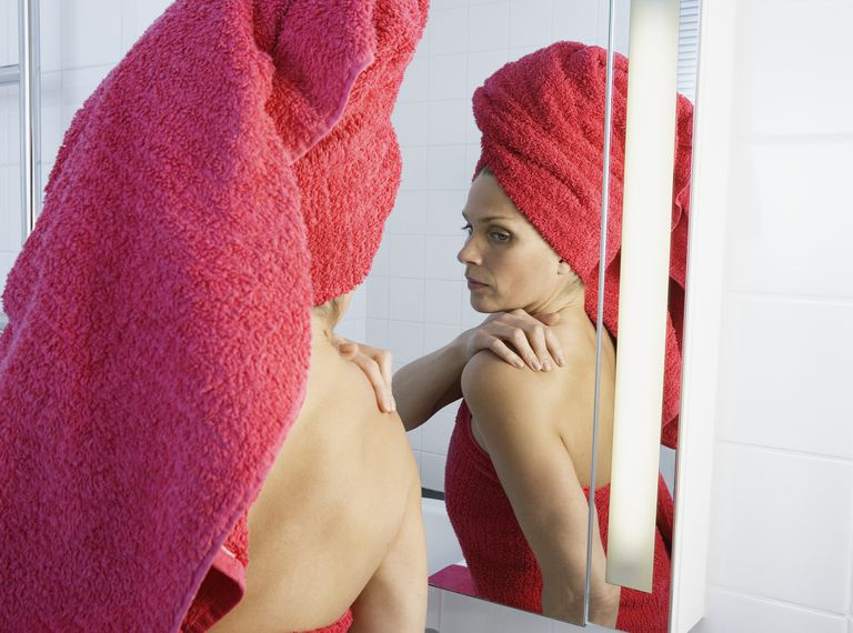 Mid adult woman wrapped in towel looking at bathroom mirror