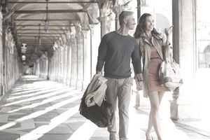 Smiling couple walking along corridor in Venice
