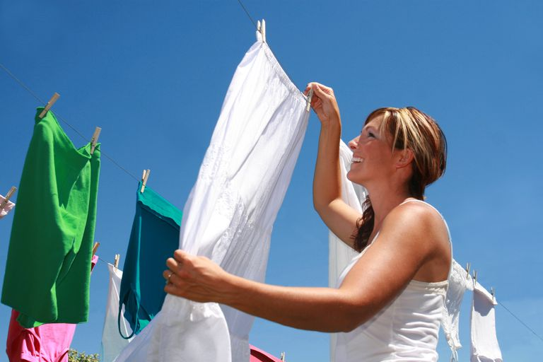 A woman hanging up white clothing to dry.