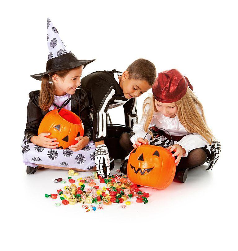 Niños con las calabazas y dulces de Halloween