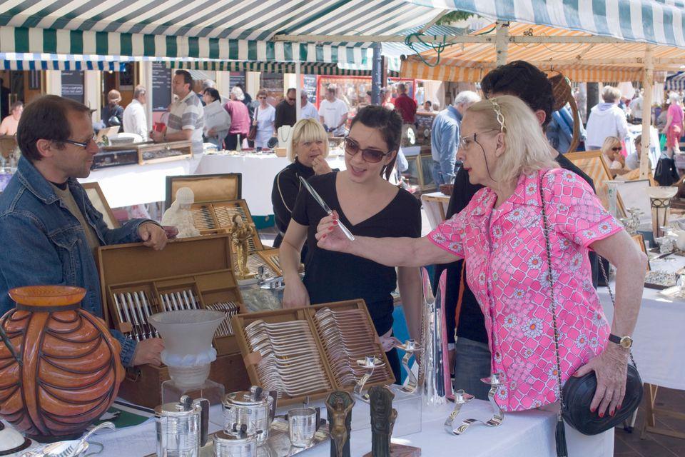haggling over antique silverware at a flea market