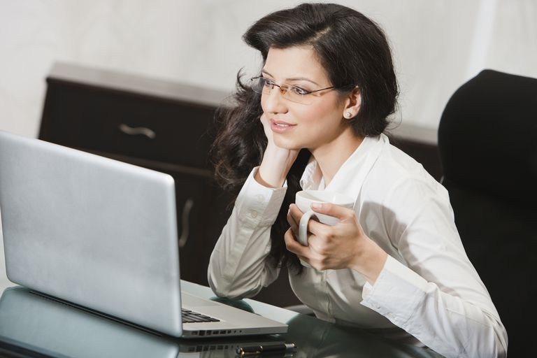 Businesswoman using laptop with drink in office