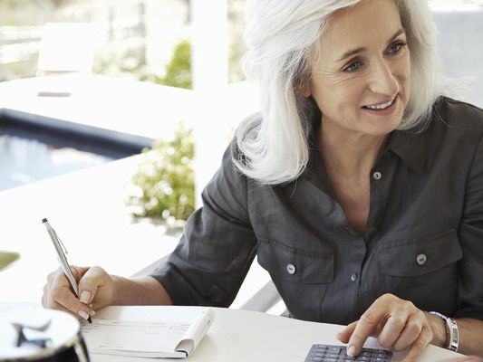 Mature woman balancing cheque book, smiling