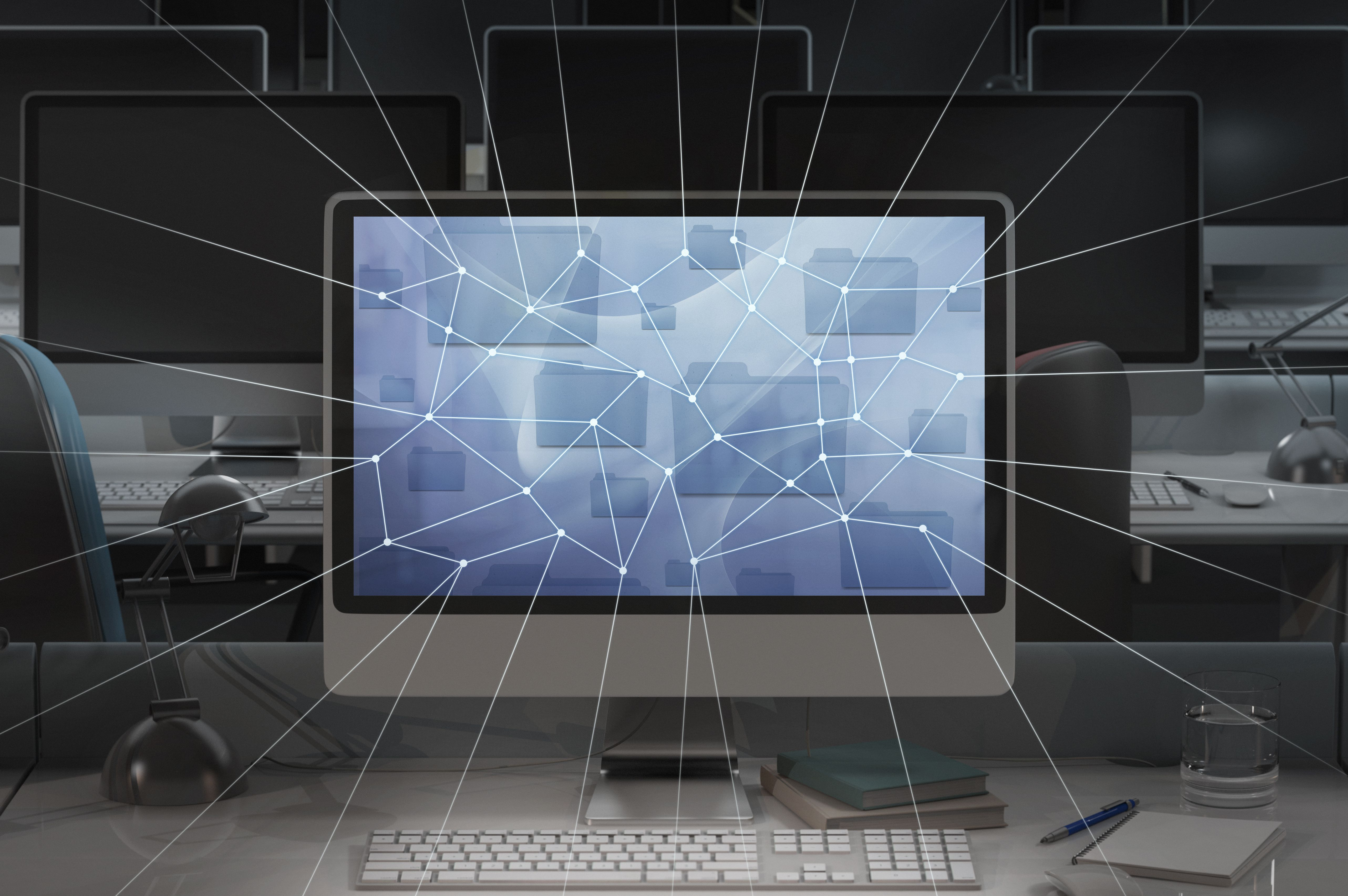 Picture of a puter in a dark office with network lines ing out of the monitor