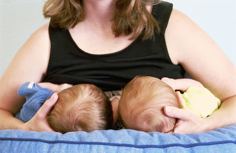Mother breastfeeding twin baby boys (3-6 months), mid section