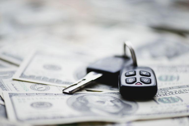 Car key on pile of one hundred dollar bills
