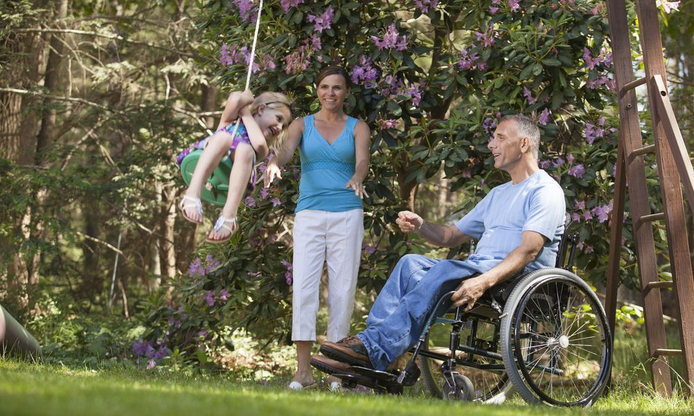 Man with Huntington's disease watching his daughter on swing along with wife