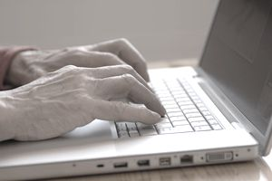Senior man using laptop, side view, close-up of hands