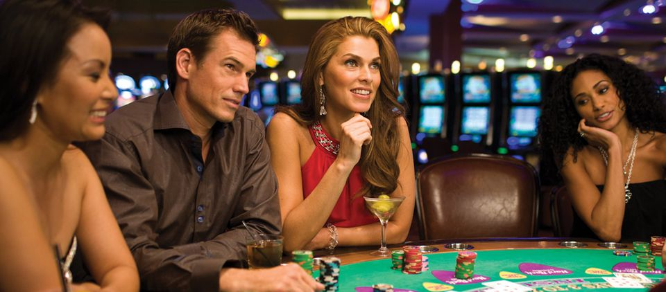Well-dressed patrons of a casino seated at a blackjack table