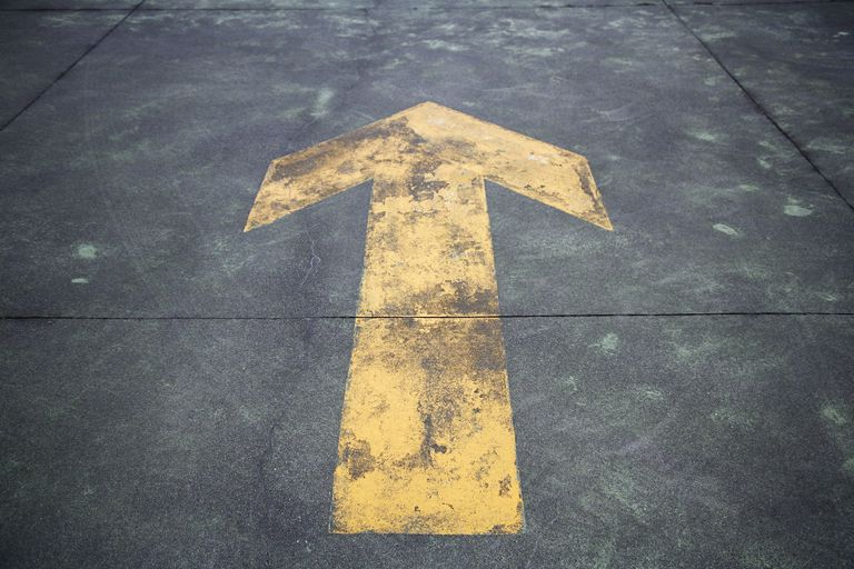 Directional arrow painted on the street, close-up