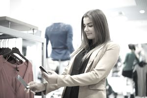 young woman checking bar code in shopping mall