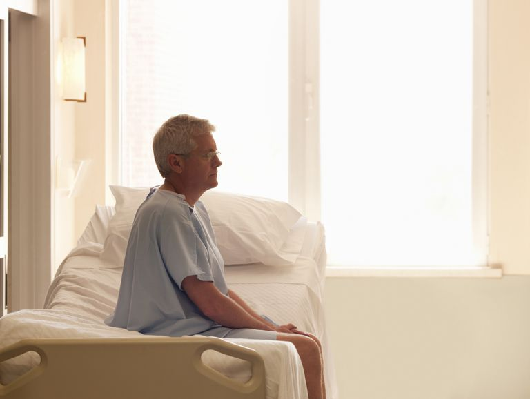 patient sitting alone on hospital bed