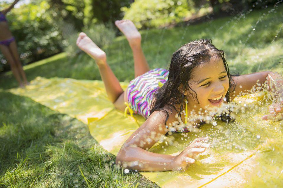 Girl on backyard slip and slide