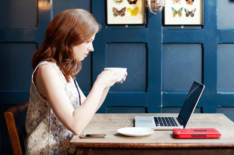 Woman looking at laptop with coffee