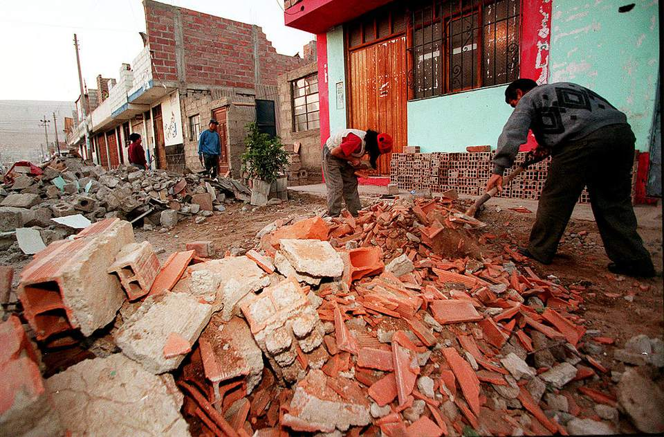 A local family cleans up after their property was destroyed by an earthquake that killed at least 50 people June 25, 2001 near Lima, Peru.