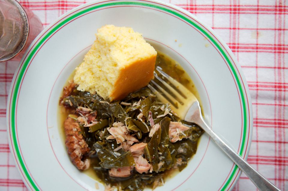 Plate of collard greens with smoked turkey wings and corn bread
