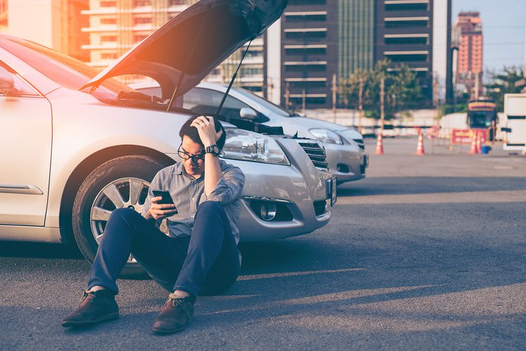 Man sitting next to broken down car