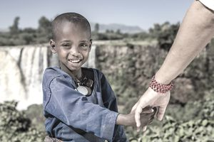 Volunteer helping young boy in Africa.