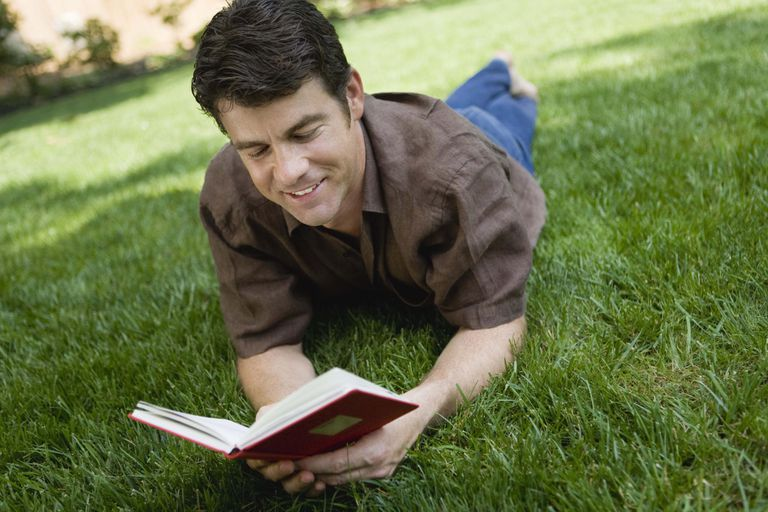 Man reading a book on lawn