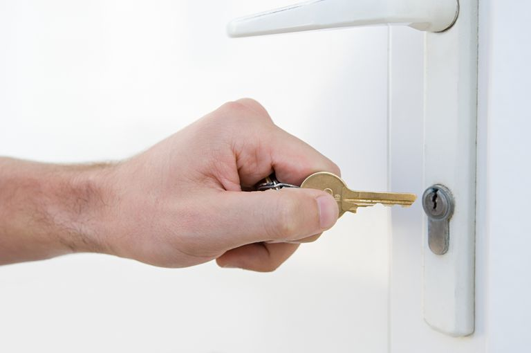 Man putting key into a lock