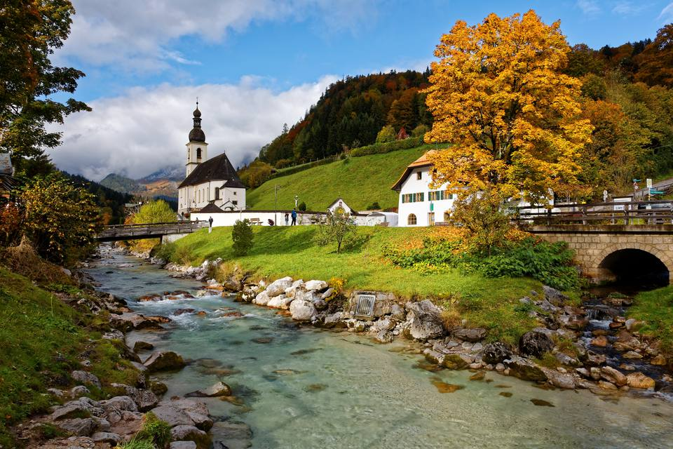 Beautiful scenery of a wooden bridge over a stream in front of a church with foggy mountains in the background ~ Picturesque autumn scenery of Bavarian countryside in Ramsau Germany