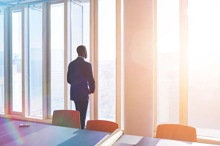 business man looking out over city from office