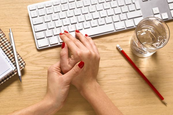 woman with hand pain working at computer