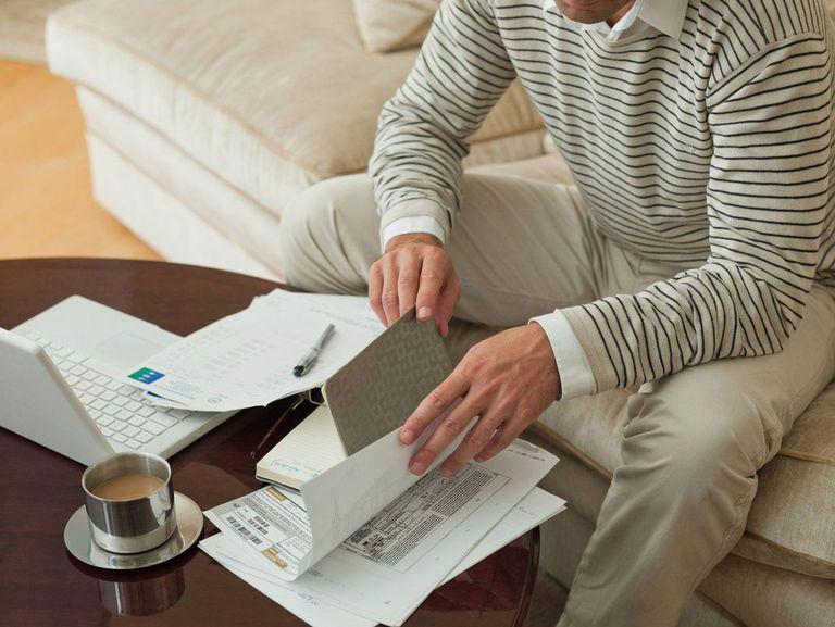 Man on sofa examining paperwork