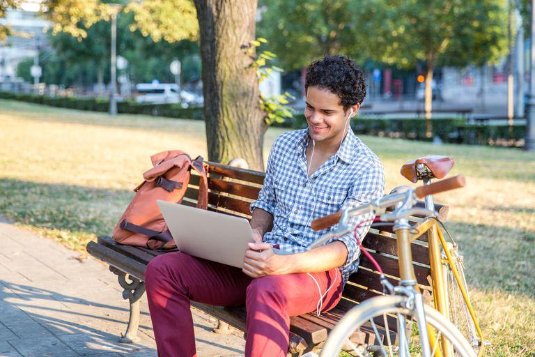 Man using laptop outside in park