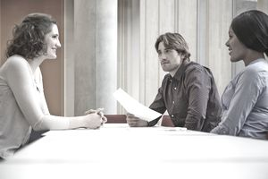 A man and woman interviewing a candidate at a table.