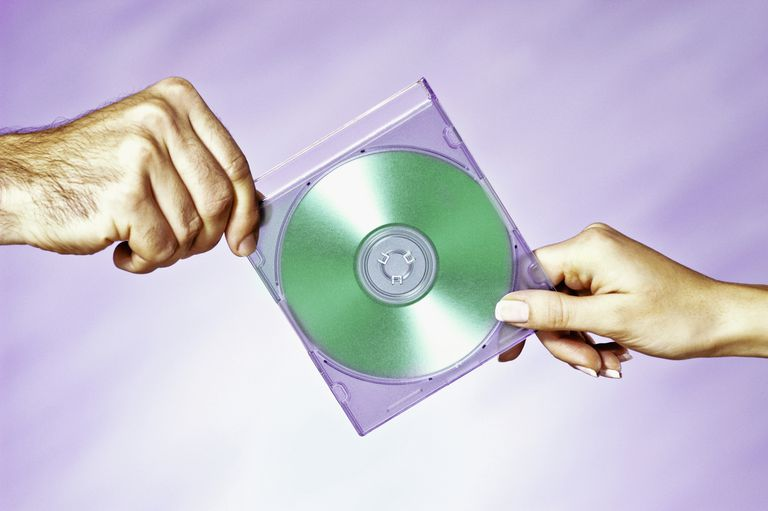 Close-up of a man and a woman holding a compact disc