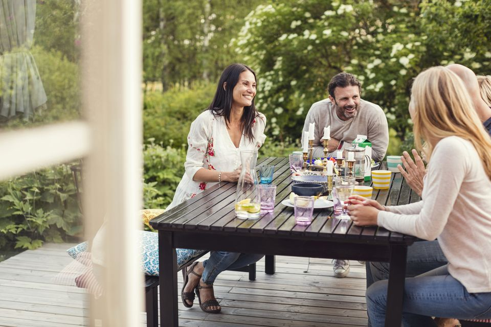 Happy family and friend sitting at dining table in back yard