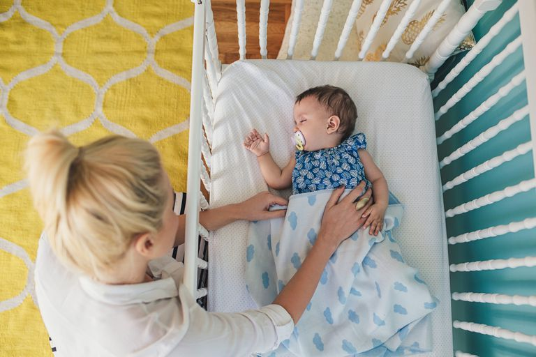 Mom putting baby to sleep in crib