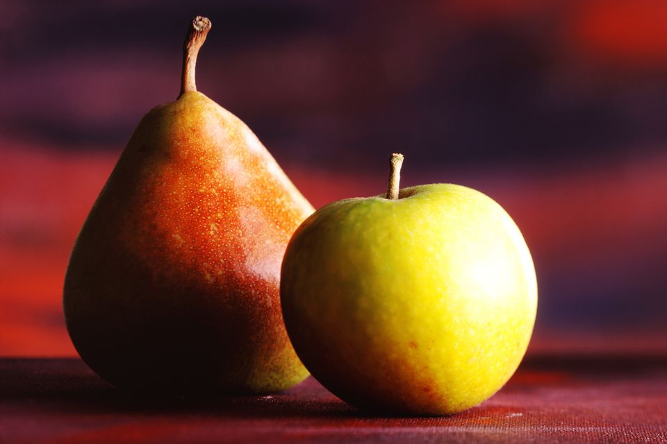 An apple and a pear on a table