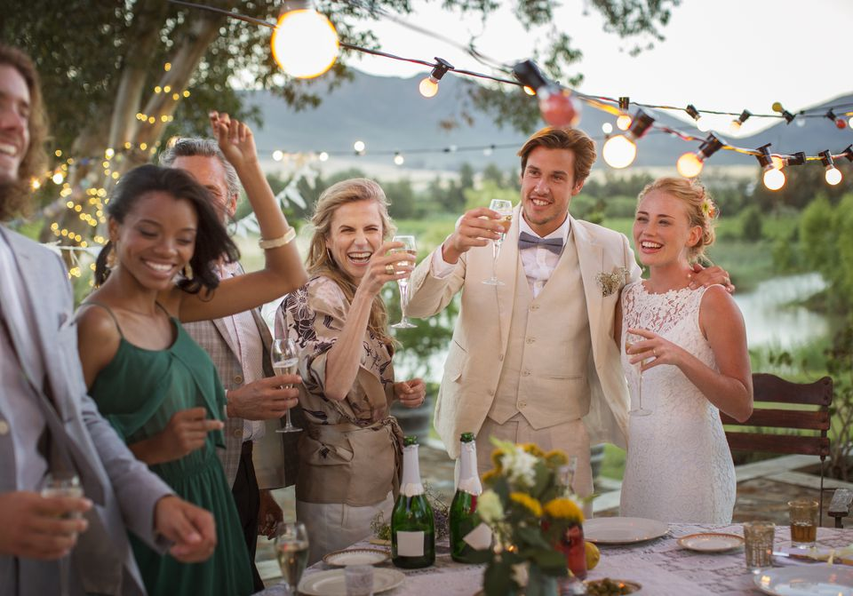 Young couple and guests toasting with champagne during wedding reception in domestic garden