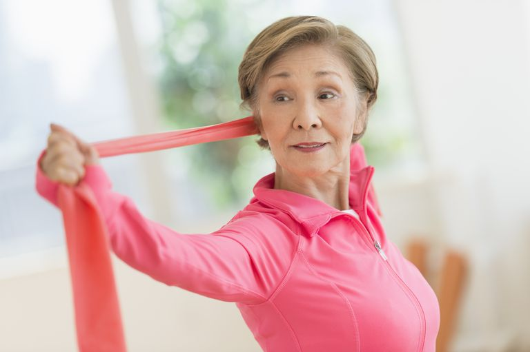 Senior woman dressed in pink does a shoulder and upper back exercise using a theraband.
