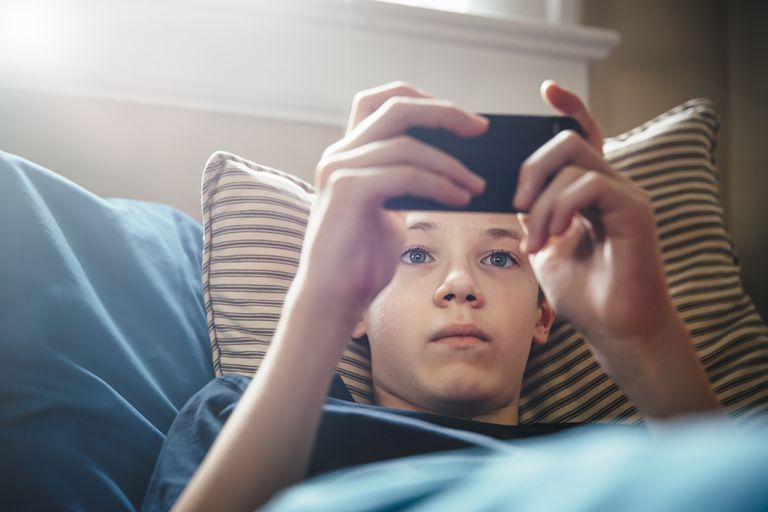 young boy using iPhone