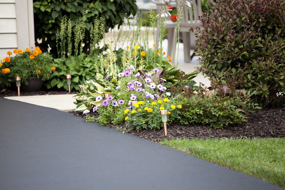 New asphalt driveway landscaped with flowers.