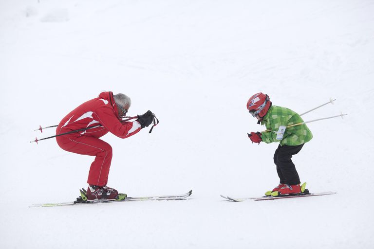 Instructor teaching ski lessons for a child