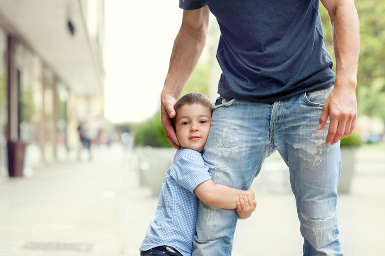Son clinging on to father's thigh