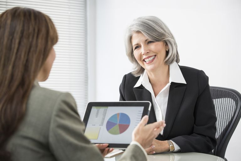 woman looking at financial information on tablet with financial advisor