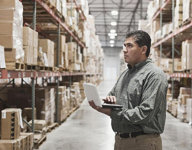 Hispanic man using laptop in warehouse