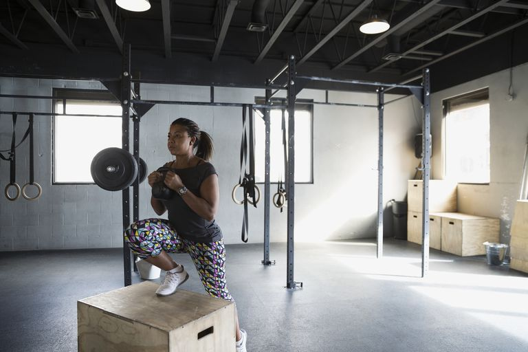Woman lunging with kettlebell on box gym