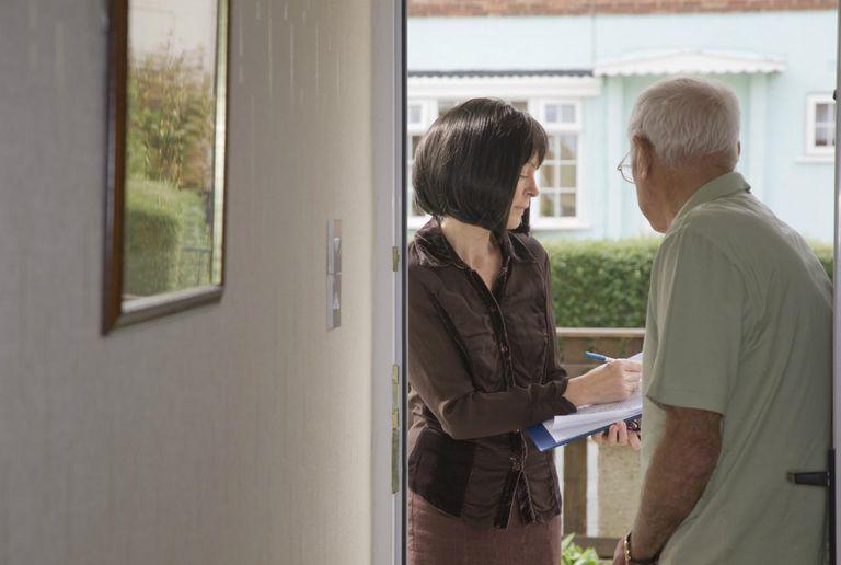 Researcher Talking To Elderly Man On The Doorstep