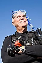 A senior scuba diver poses on the surface wearing full scuba diving gear, mask, BC, and wetsuit