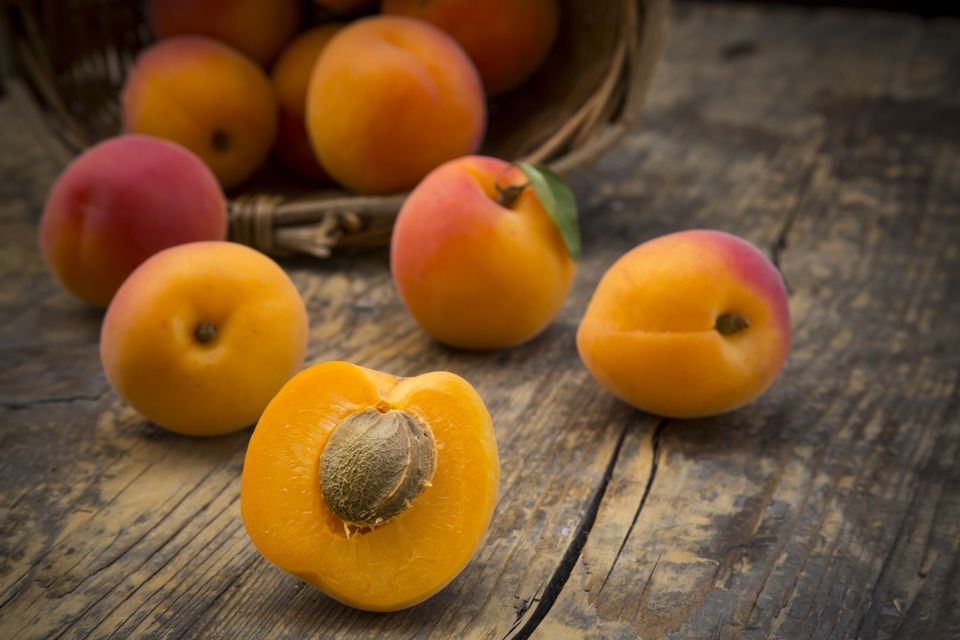 Sliced and whole apricots on wood