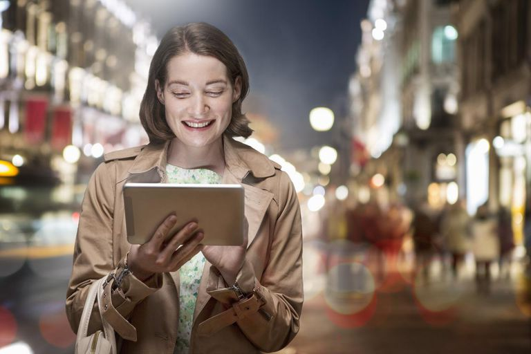 Woman looking at handheld computer in busy street.