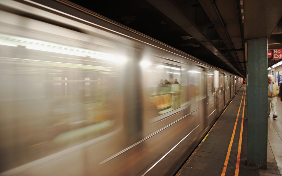 A subway car racing through a station in New York.