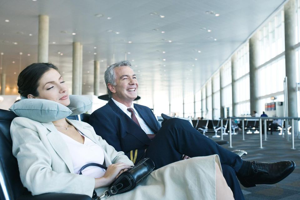 Business travelers sitting in airport lounge, woman napping with neck pillow next to smiling man
