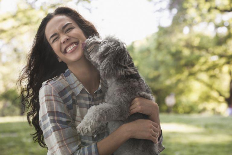 Mujer joven con perro en brazos